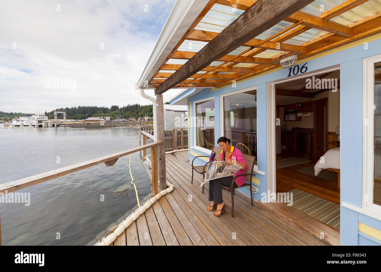 A visitor staying at the Seine Boat Inn relaxes on the waterfront balcony.  Alert Bay. - Stock Image