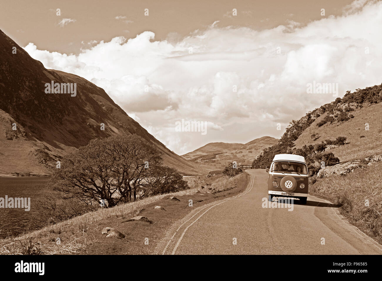 Classic VW campervan on road next to Crummockwater, Lake District National Park, Cumbria, England UK - Stock Image