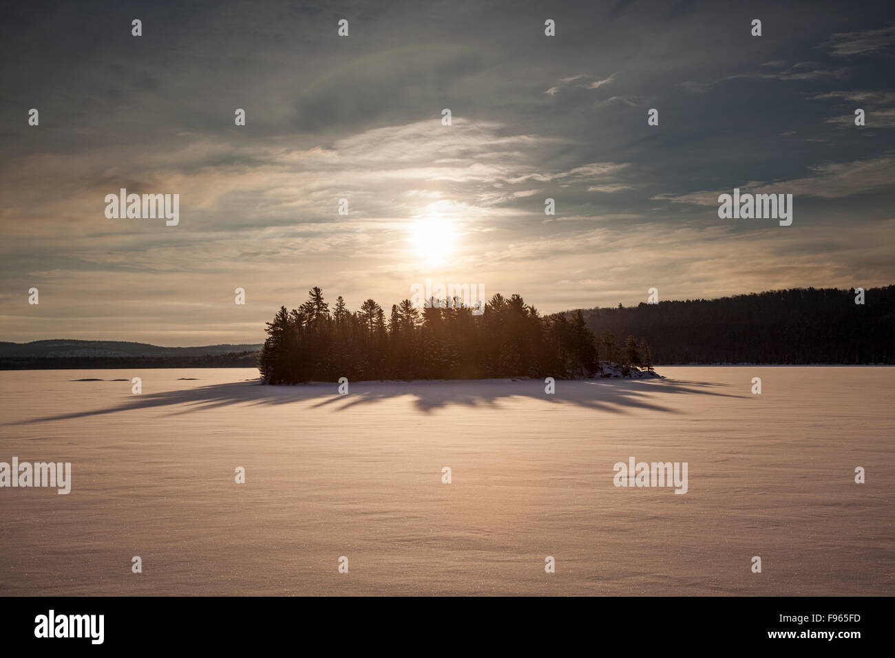 Sun rising over an island in the frozen Lake of Two Rivers, Algonquin Provincial Park, Ontario, Canada - Stock Image