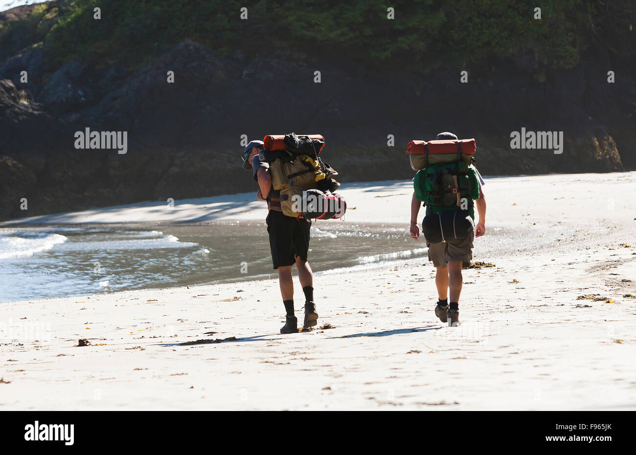 Two hikers stroll along the beach at San Jose Bay, looking for a campsite for the night.  San Jose Bay. - Stock Image