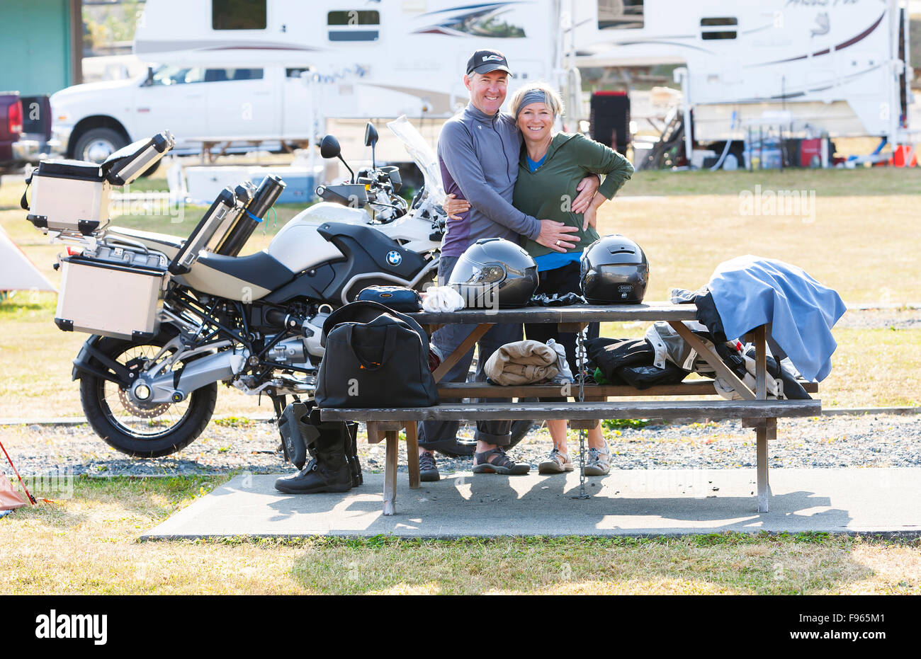 a happy mature couple packs up their campsite in preparation for a days ride on the North Island. Stock Photo