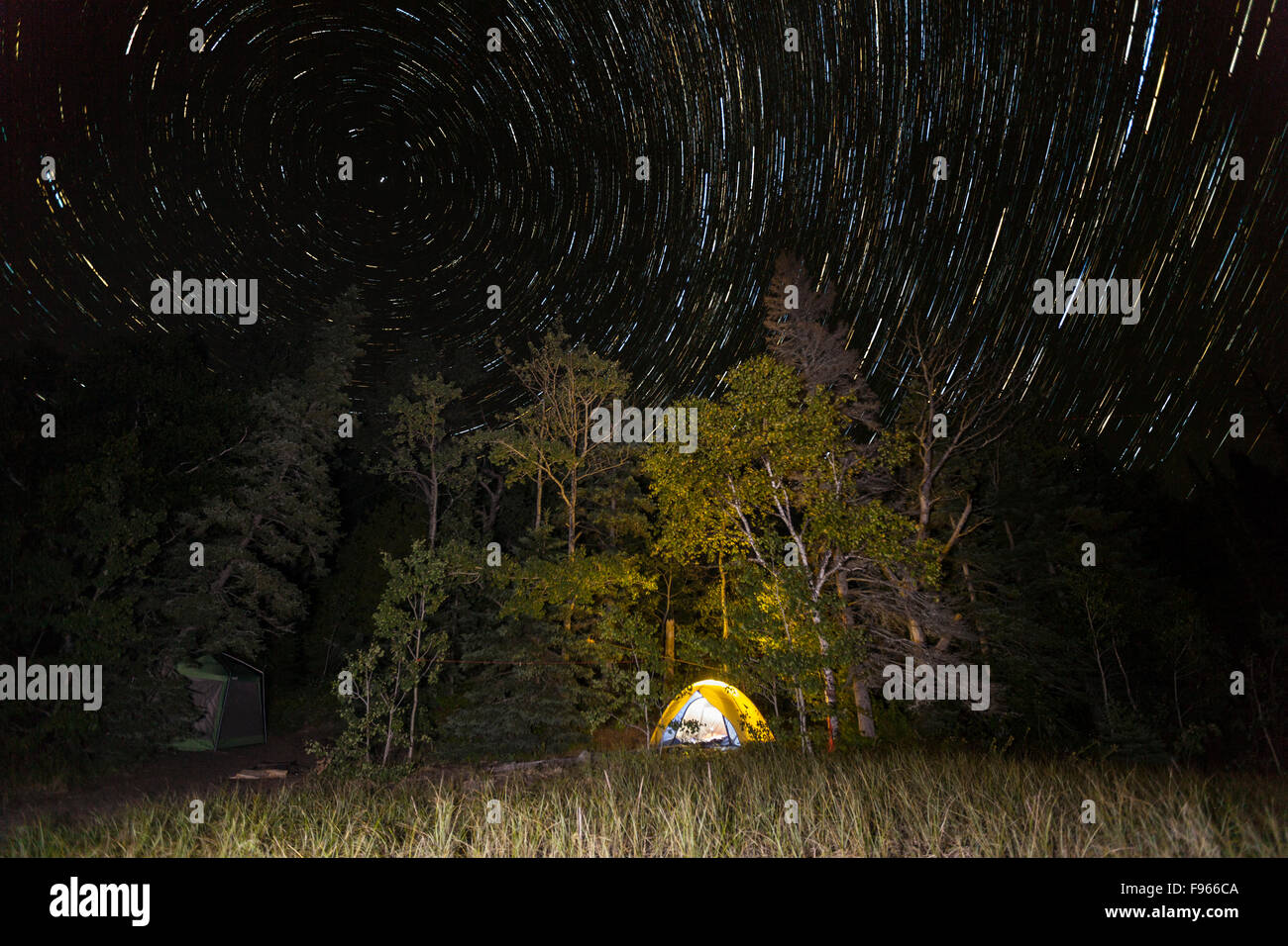 Star trails over a Lake Superior campsite in Lake Superior Provincial Park, Ontario, Canada (image stacking) Stock Photo