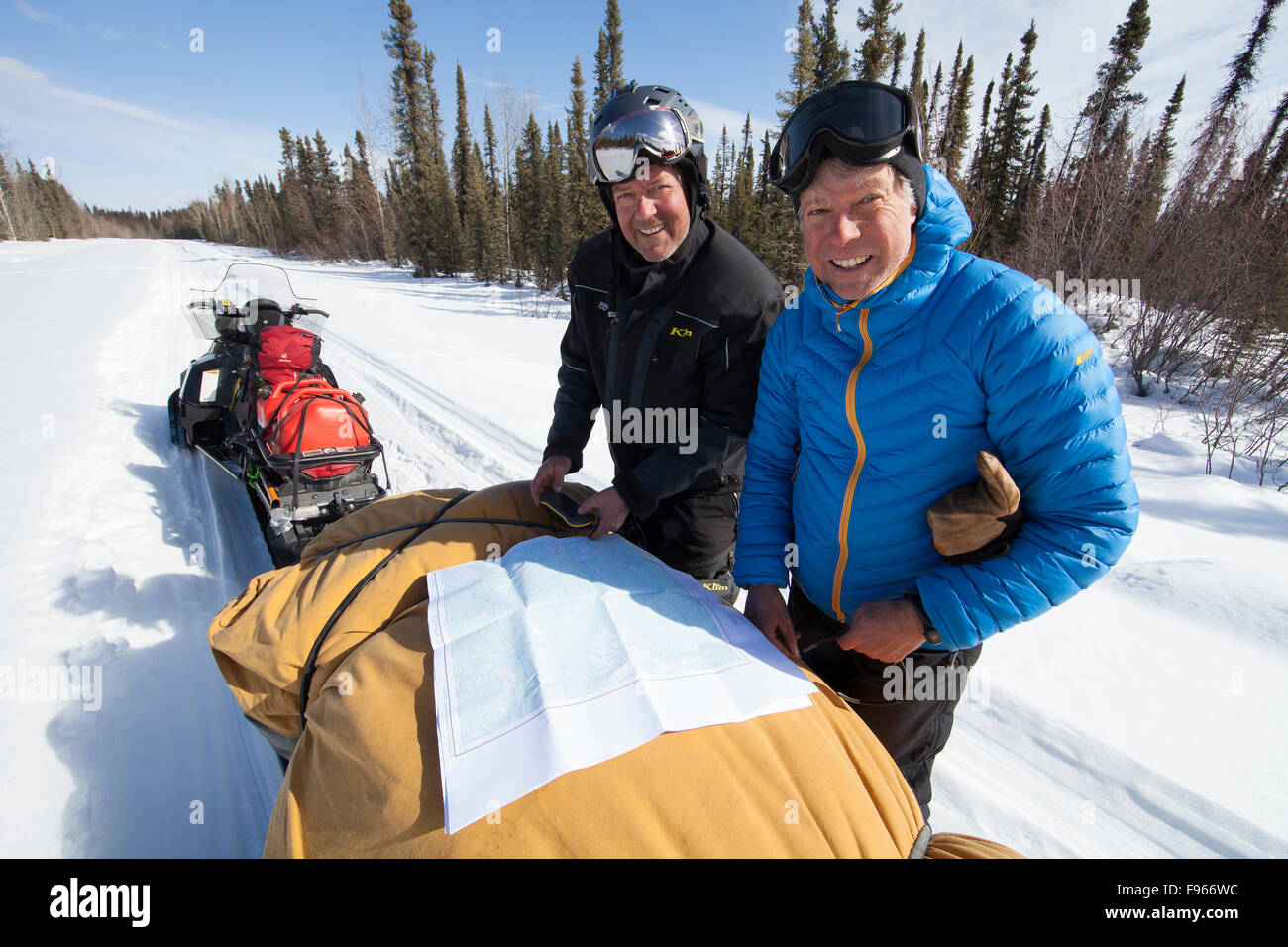 Two snowmobile friends check out a map while traveling along the North Canol Trail.  Near Ross River, Yukon Territory. - Stock Image