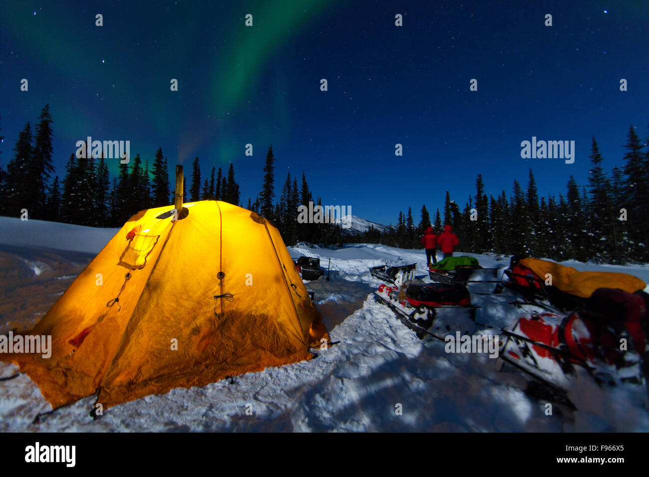 Snowmobilers watch Northern Lights (Aurora Borealis) dance in a northern sky while traveling along the North Canol - Stock Image