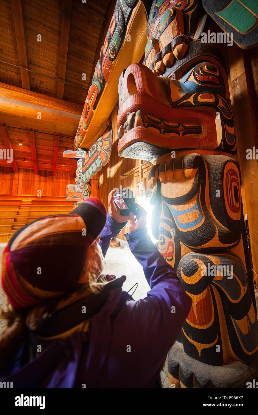 A visitor to the Klemtu Bighouse photographs one of the large corner posts in the first nations structure.  Klemtu, Stock Photo