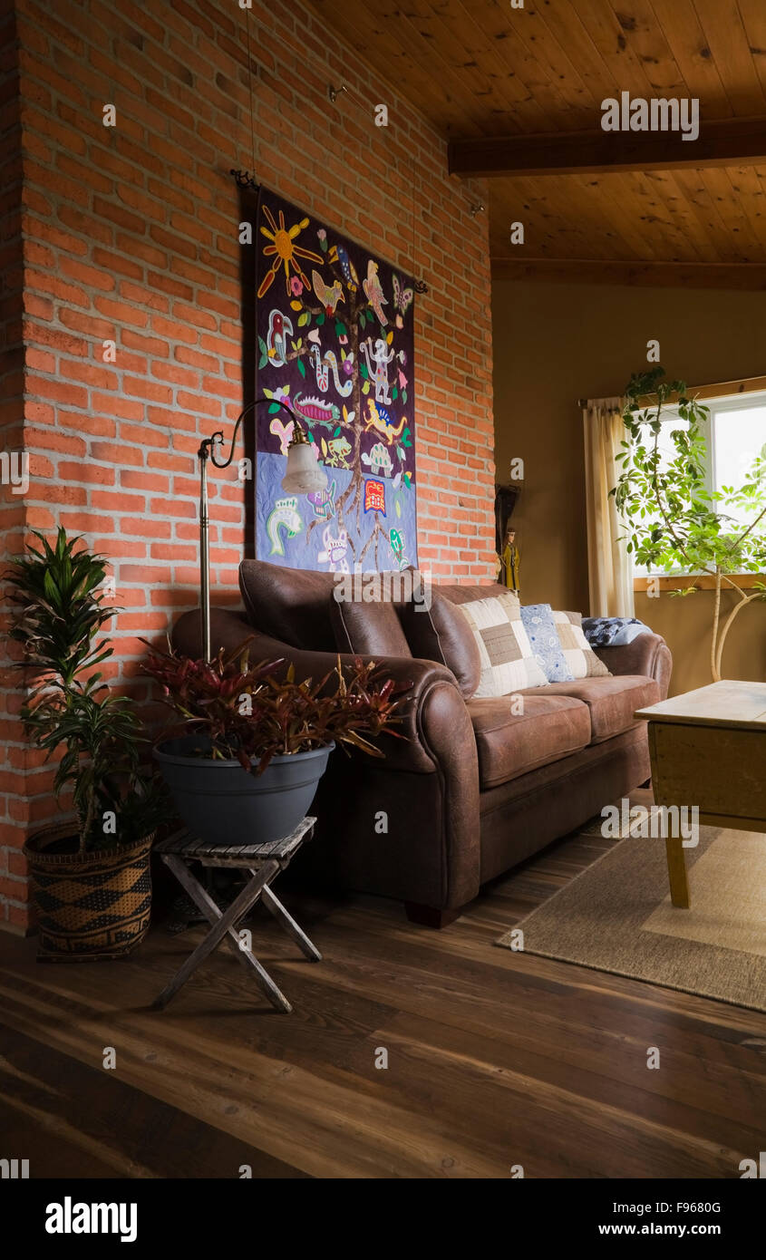 Exceptionnel Brown Leather Sofa Against A Red Brick Wall And An Antique Wooden Table In  A Living Room On The Upstairs Floor Inside A Country