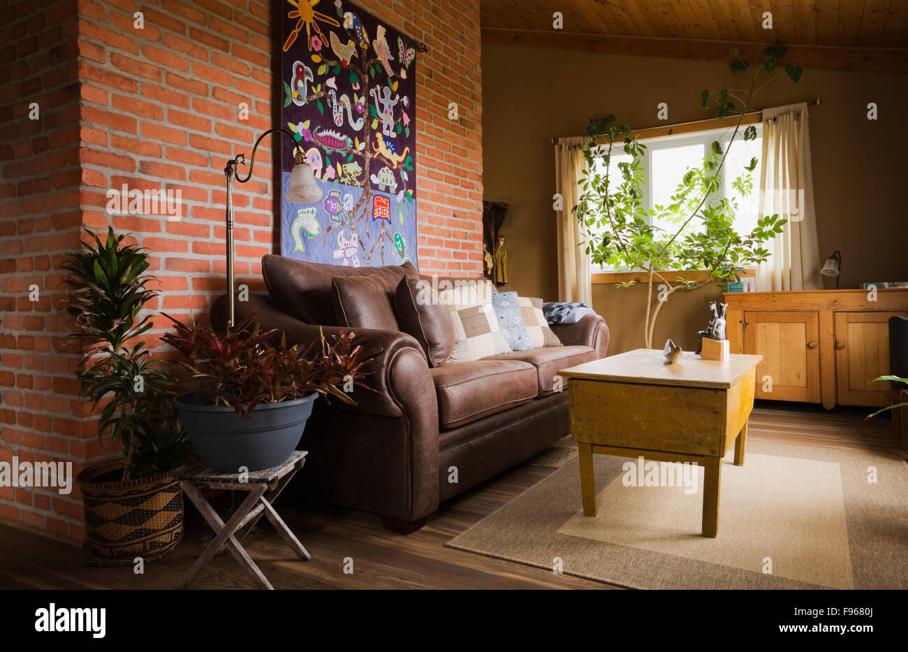 Brown leather sofa against a red brick wall and an antique wooden ...