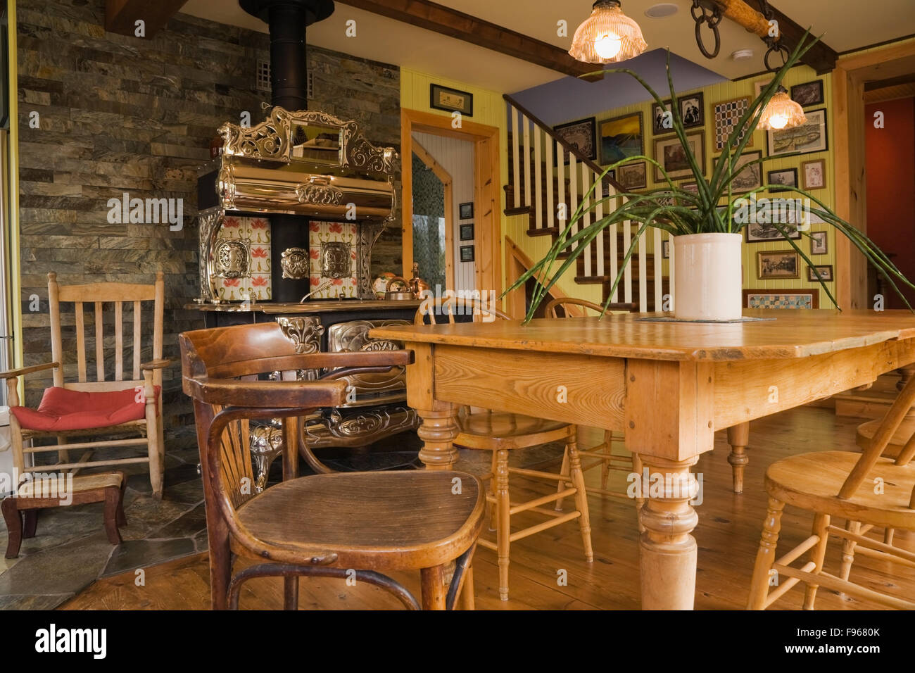Wooden Dining Table With Chairs And An Old Wooden Rocking Chair Next To An  Antique Royal Model Wood Cooking Stove In The Dining