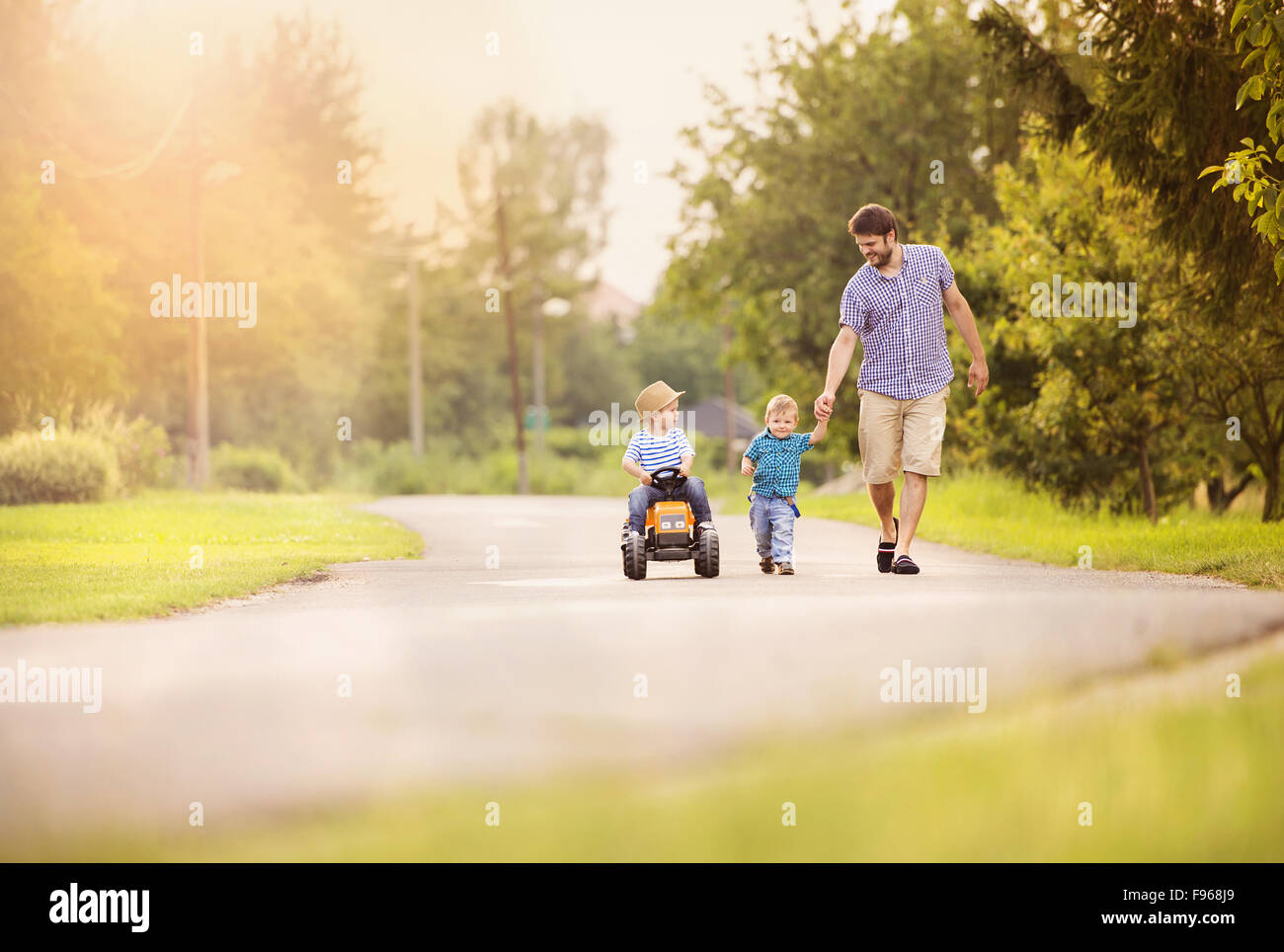 Happy young father with his two little sons have fun on road, one boy is riding on little tractor, other boy is - Stock Image
