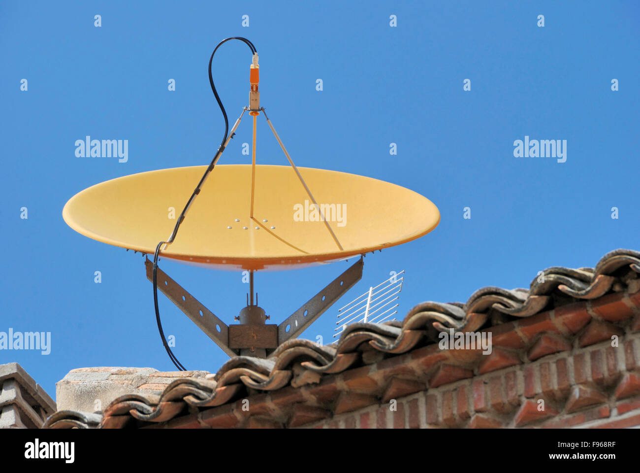 Satellite dish on the roof of a house Stock Photo