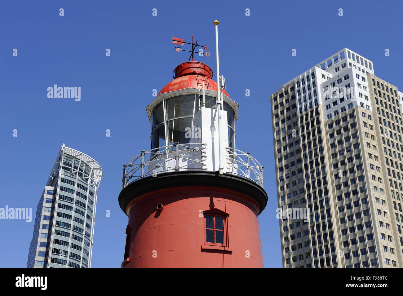 Lighthouse between two sky scrapers against clear blue sky - Stock Image
