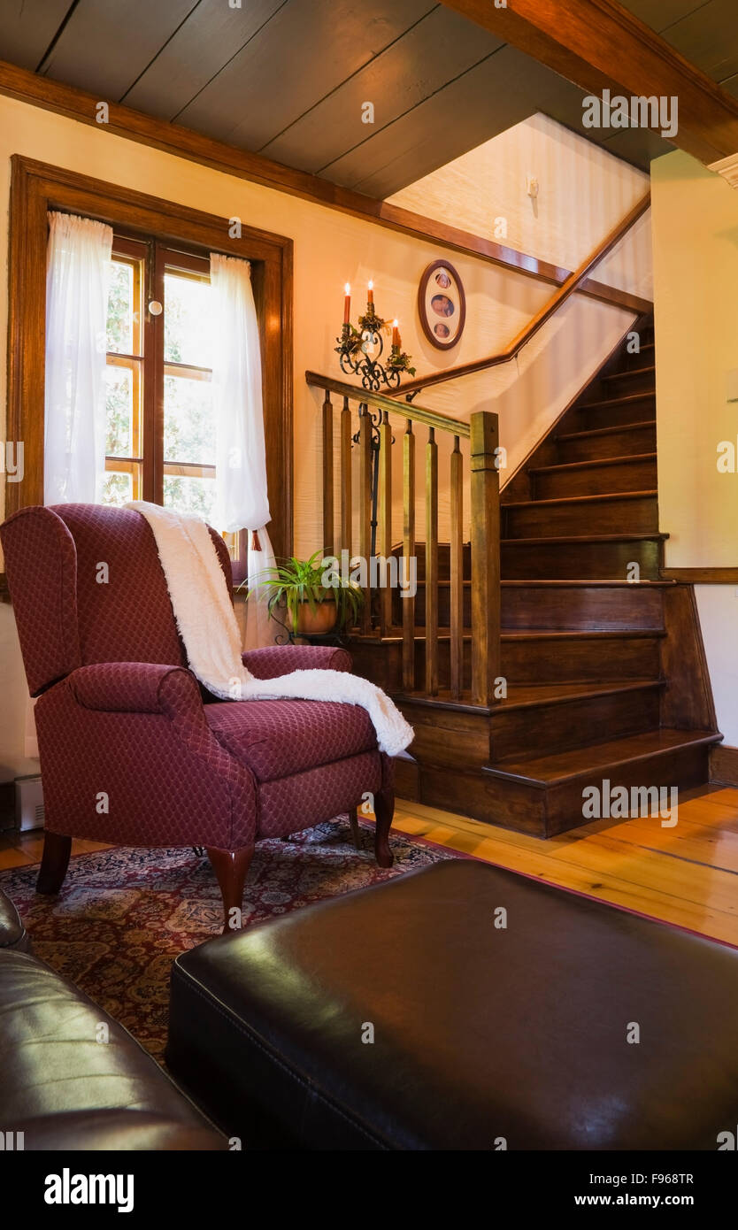 Leather sofa with footstool and a upholstered chair next to the wooden staircase in the living room inside a reconstructed - Stock Image