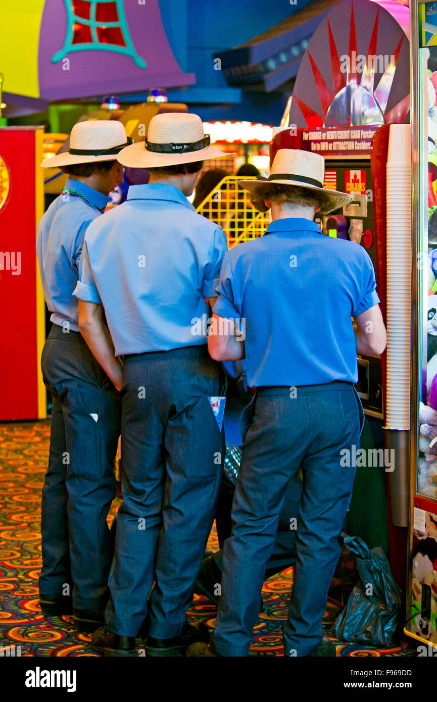 Young mennonites at video arcade in Cliffton Hill entertainment district in Niagara Falls, Ontario - Stock Image