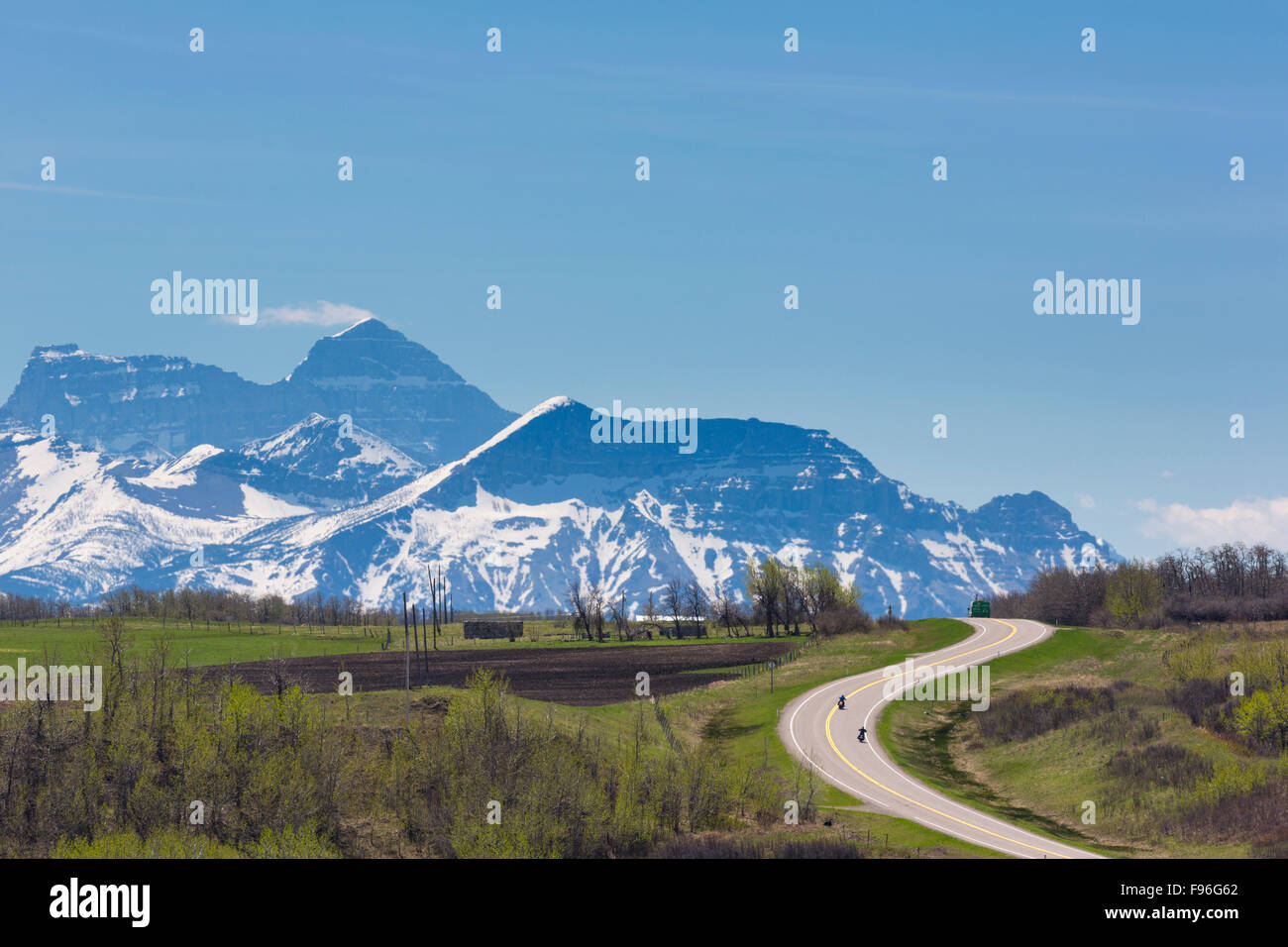 Motorcycles on highway with Water Lakes National Park in background, Alberta, Canada - Stock Image