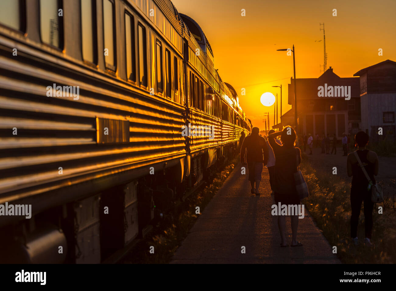 Sun setting in front of passenger train stopped in the town of Melville in Saskatchewan, Canada. - Stock Image