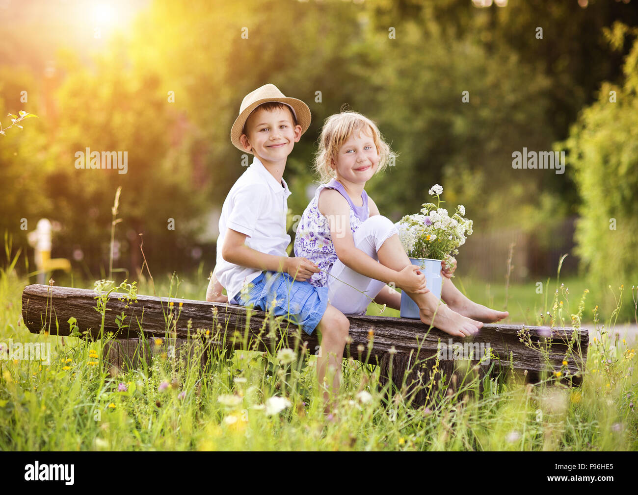 cute boy and girl in love. they sitting on bench at sunset stock