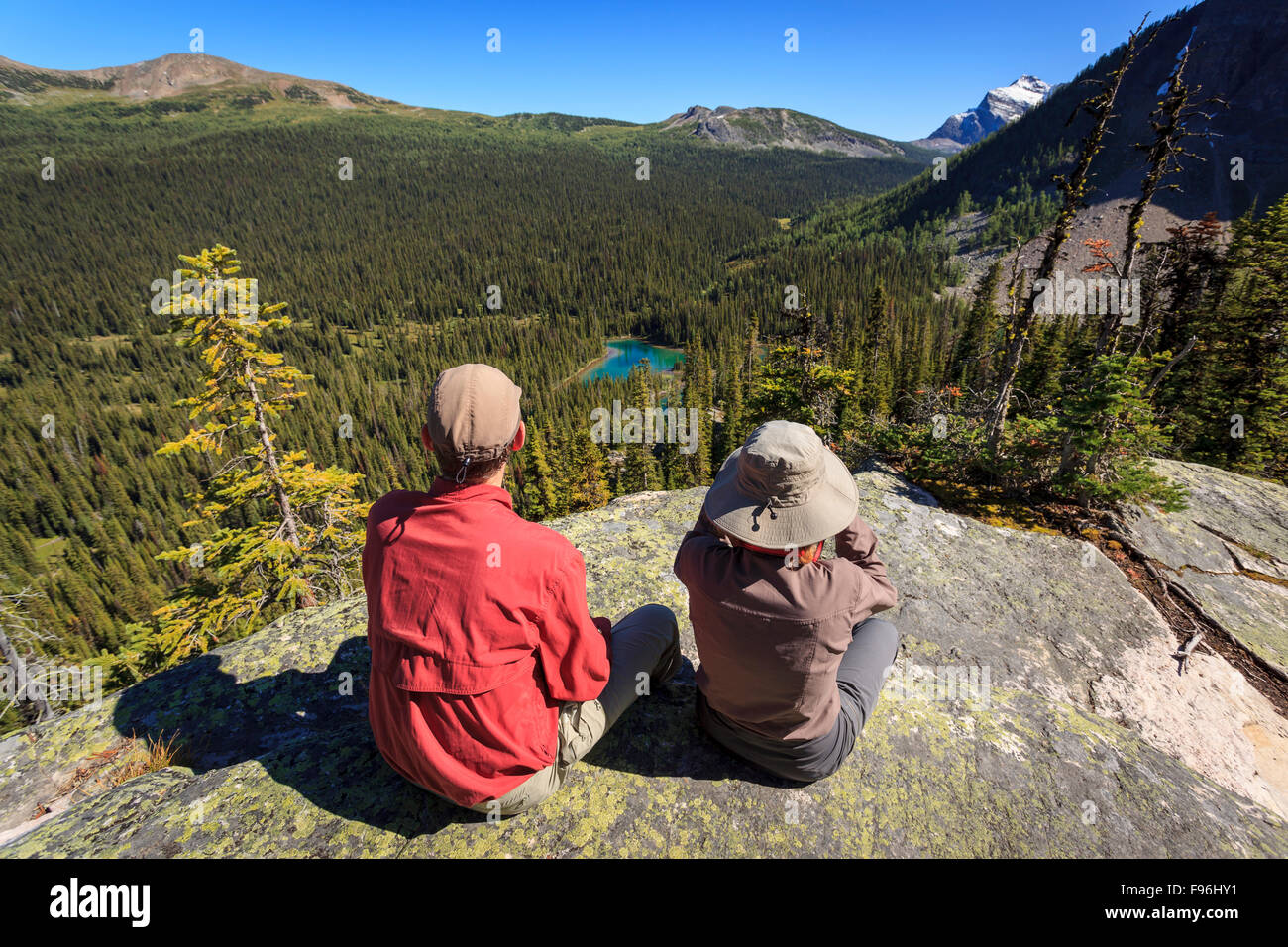 Two hikers rest at a viewpoint overlooking Egypt Lake in Banff National Park, Alberta, Canada. Model Released. - Stock Image