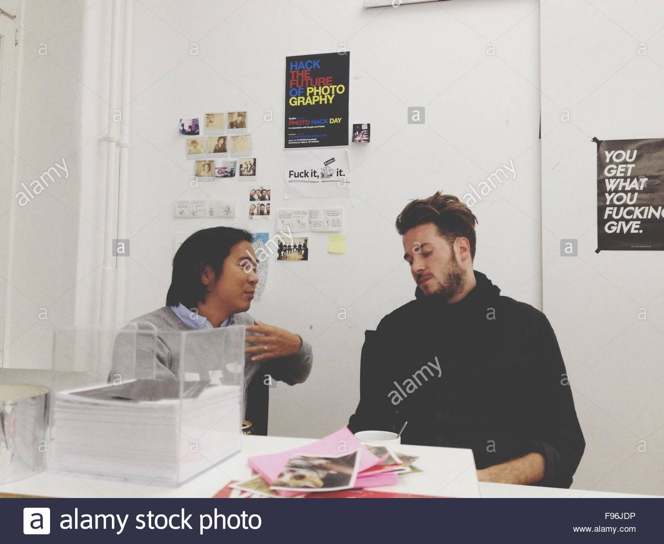 Two Young Men Discussing At Office Desk - Stock Image