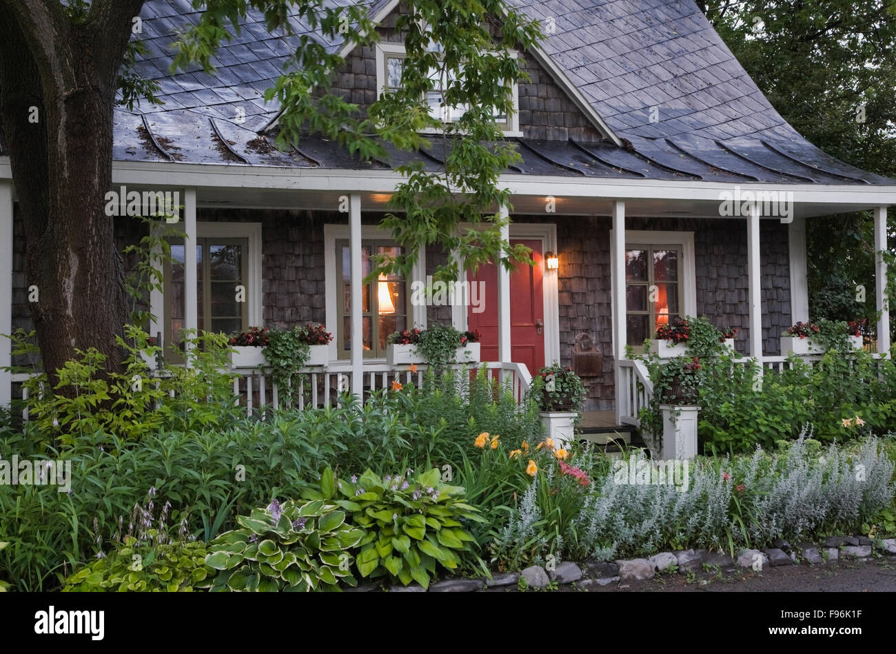 Old 1809 Weathered Cedar Shingles With White Trim Cottage Style Residential Home Facade At Dusk In Summer Quebec Canada This
