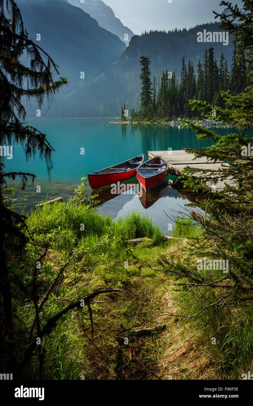 brightly colored canoes tied to a dock at Lake O'Hara in Yoho National Park in the Canadian Rockies - Stock Image