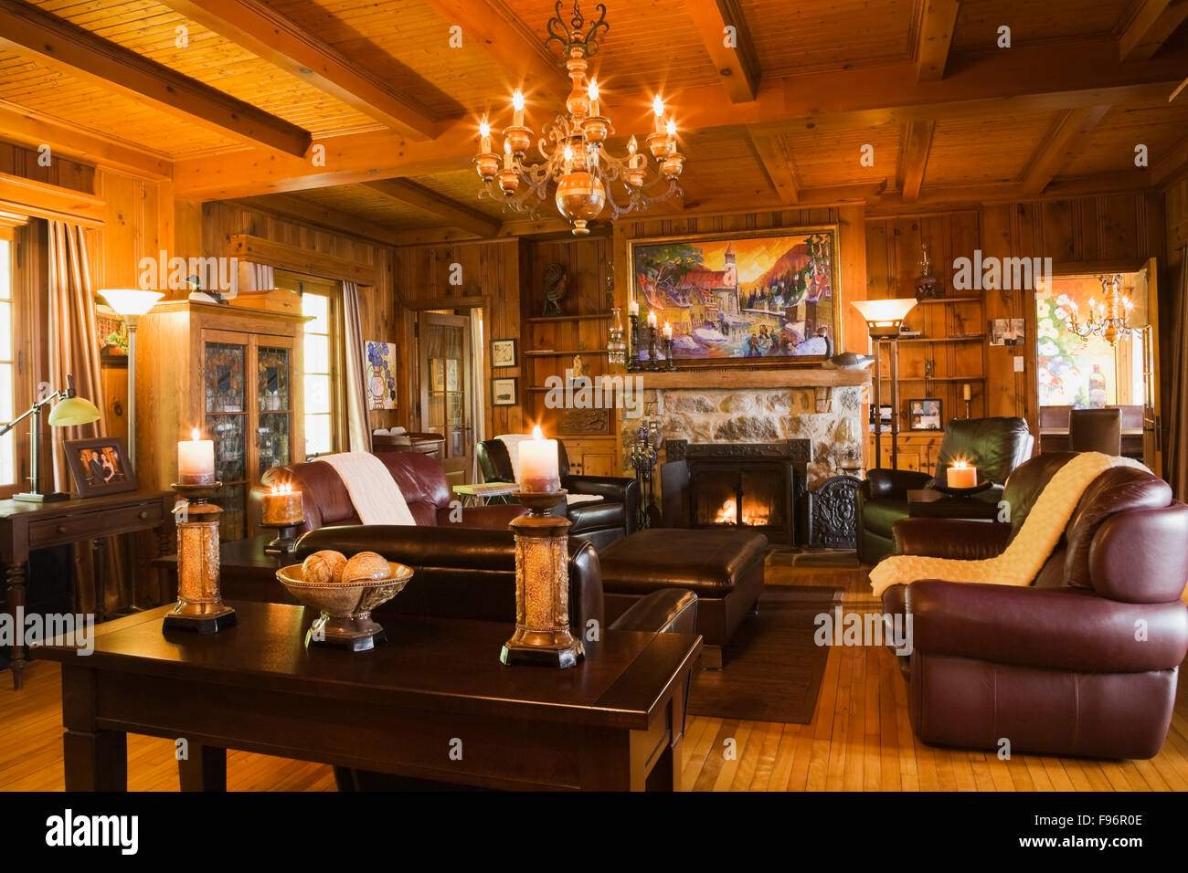 Lit Stone Fireplace And Brown Leather Chairs And Sofas In The Living Room  Inside A 1920s Cottage Style Old Home. Quebec, Canada