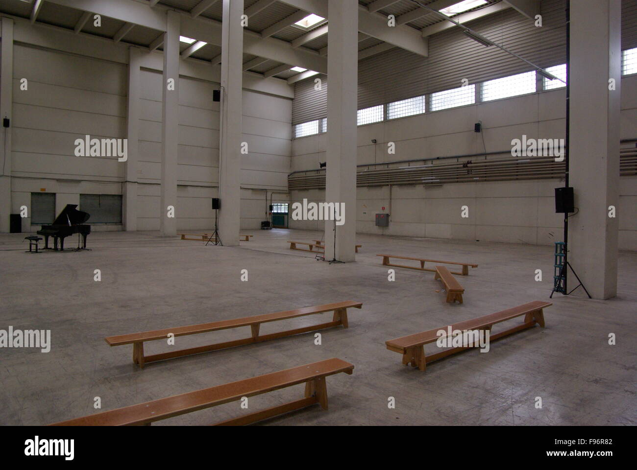 Grand Piano And Wooden Benches In Spacious Empty Hall - Stock Image