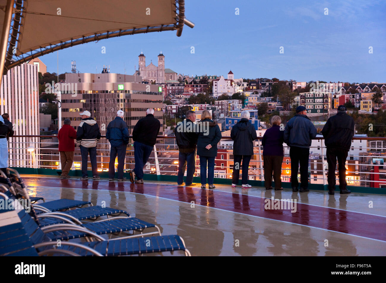As their cruise ship begins docking maneuvers, a row of passengers gaze at the city of St. Johns, Newfoundland, - Stock Image