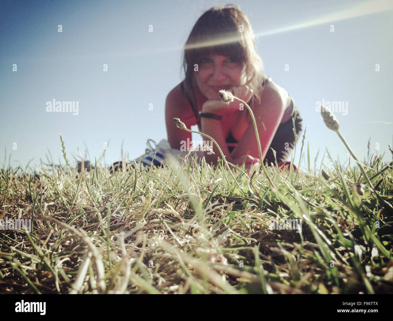 Portrait Of Woman With Hand On Chin While Sitting On Grasses - Stock Image