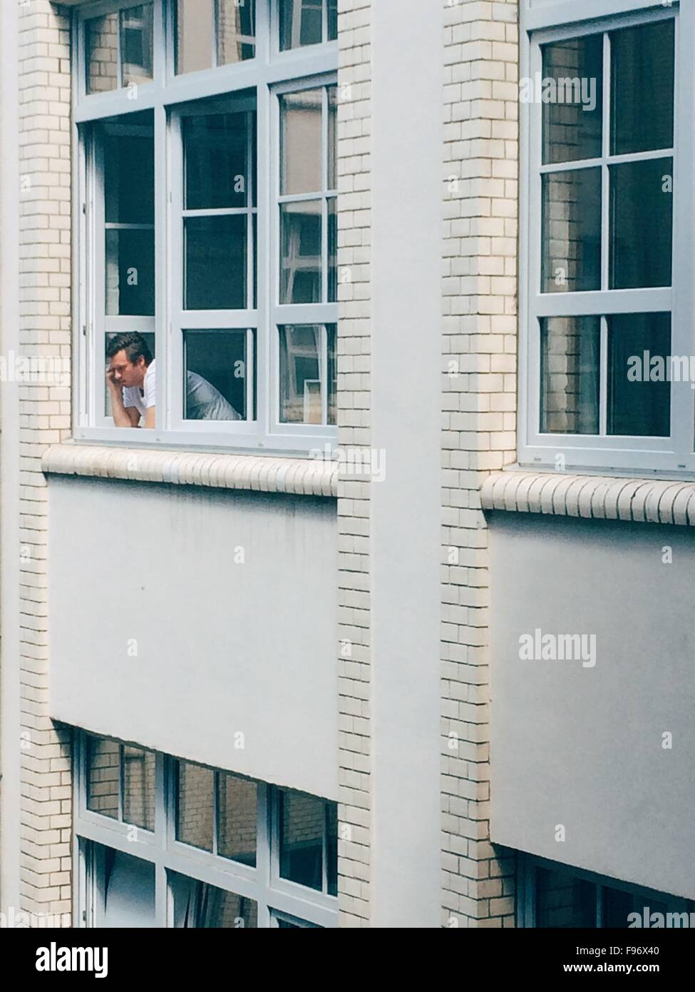 Low Angle View Of A Man Looking Out Of Window - Stock Image