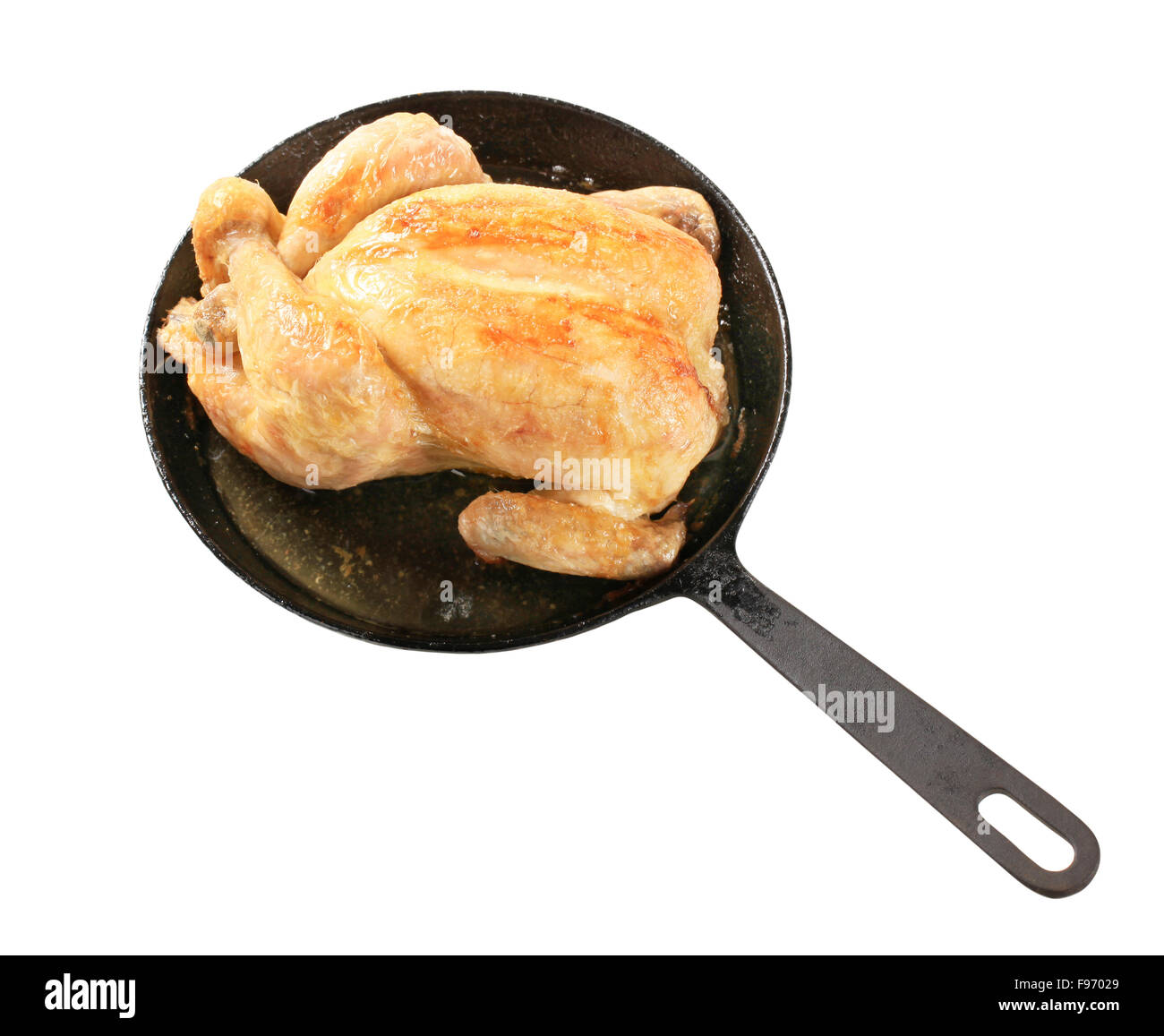 Baked chicken on an iron skillet - Stock Image