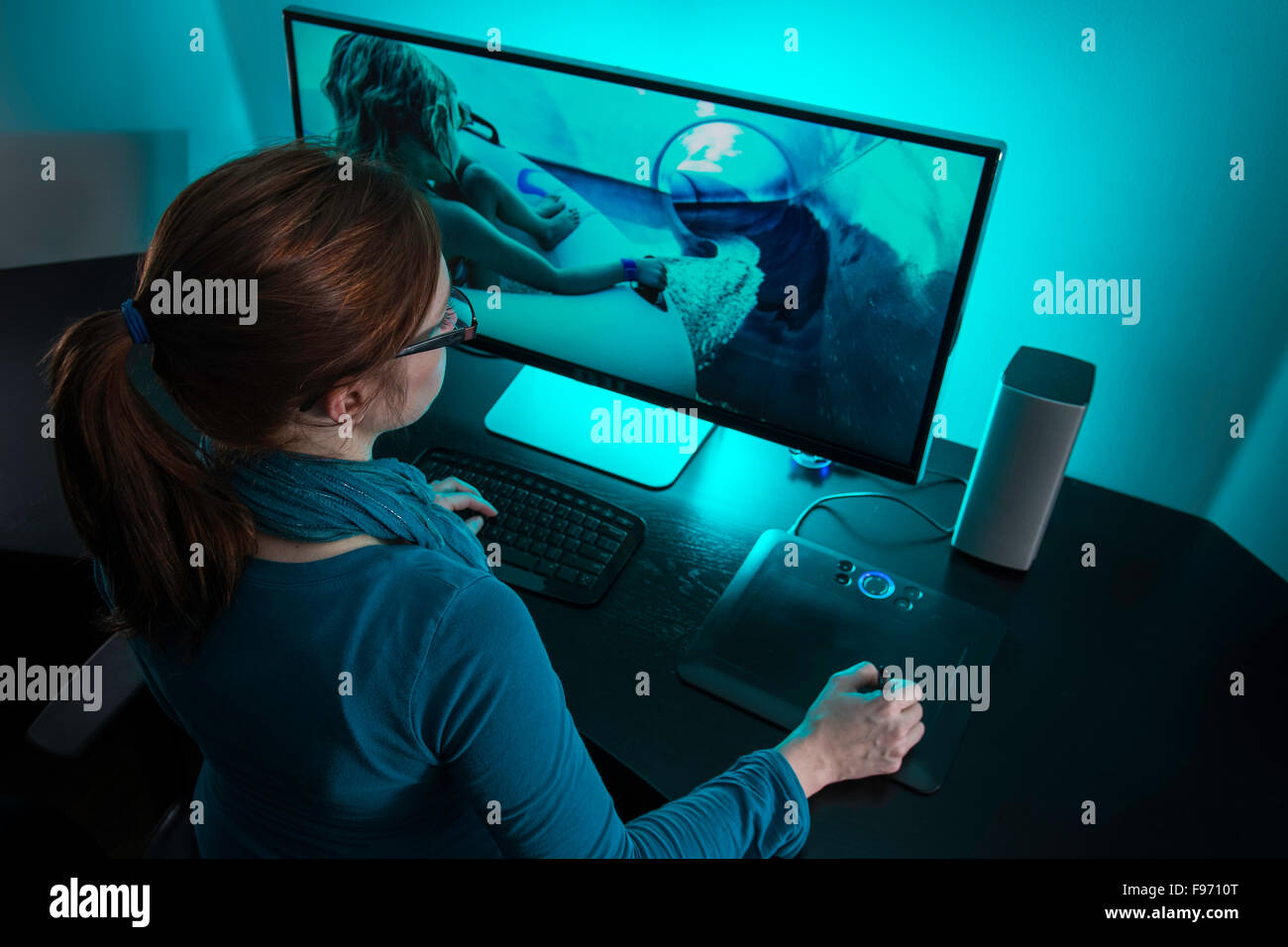 Woman (35) editing photography on a desktop PC in her home office. - Stock Image