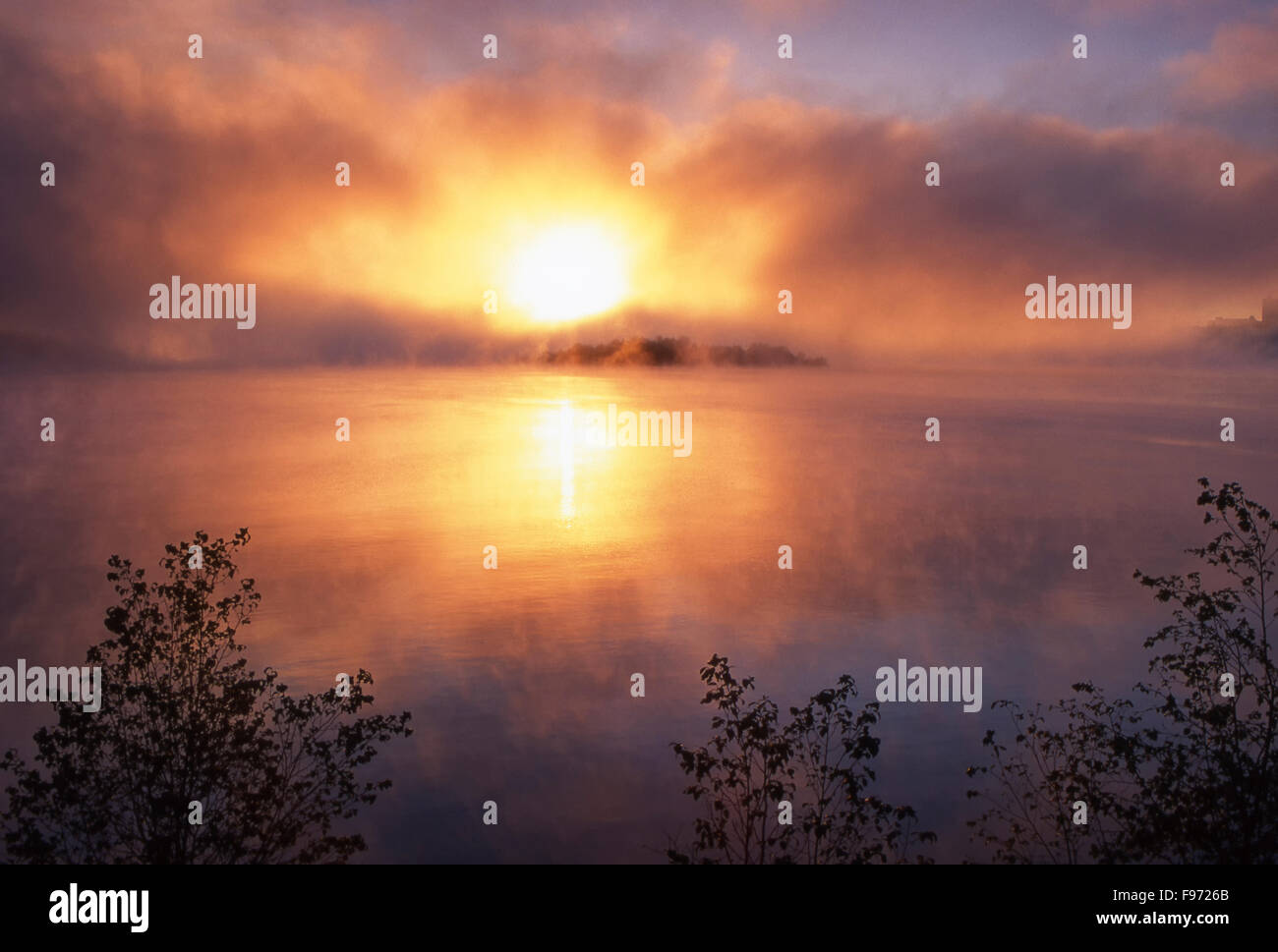 Sunrising through fog bank over Ramsey Lake, Sudbury, Ontario, Canada - Stock Image