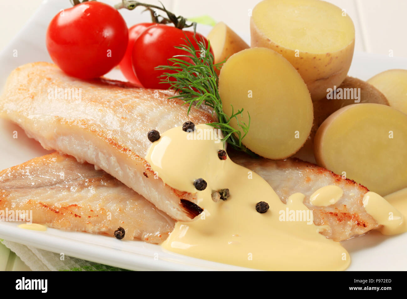 White fish fillets with new potatoes and Hollandaise sauce - Stock Image
