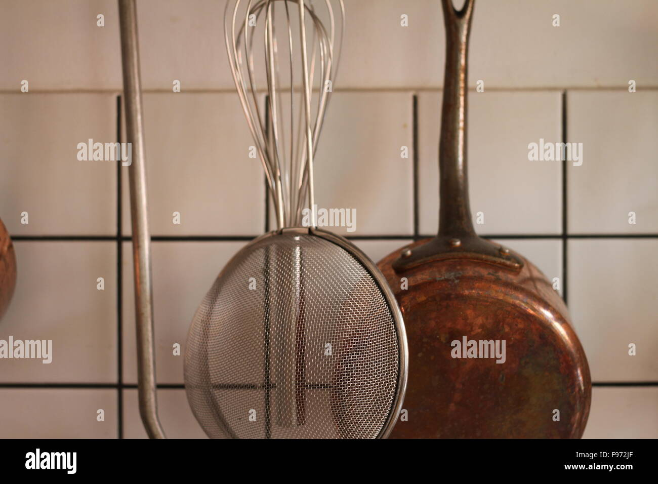 Hanging Brass Kitchen Utensils - Stock Image