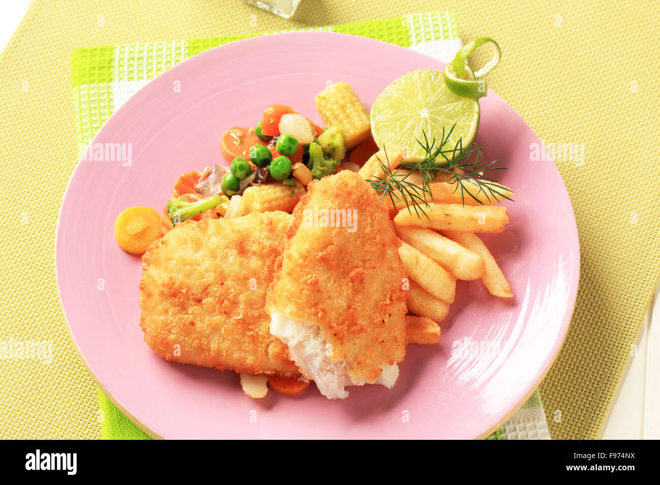 Fried breaded fish fillets with  mixed vegetables and French fries - Stock Image