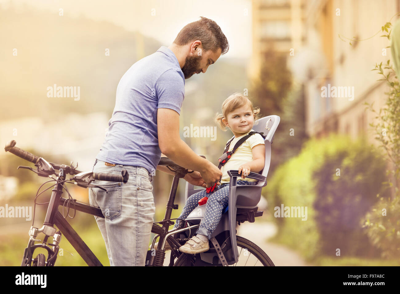 Young father with his little daughter on bicycle in green sunny park - Stock Image