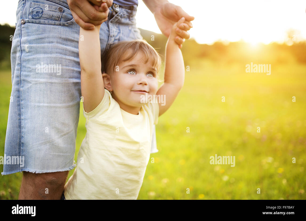 Hipster father playing with his little daughter in the green park. - Stock Image