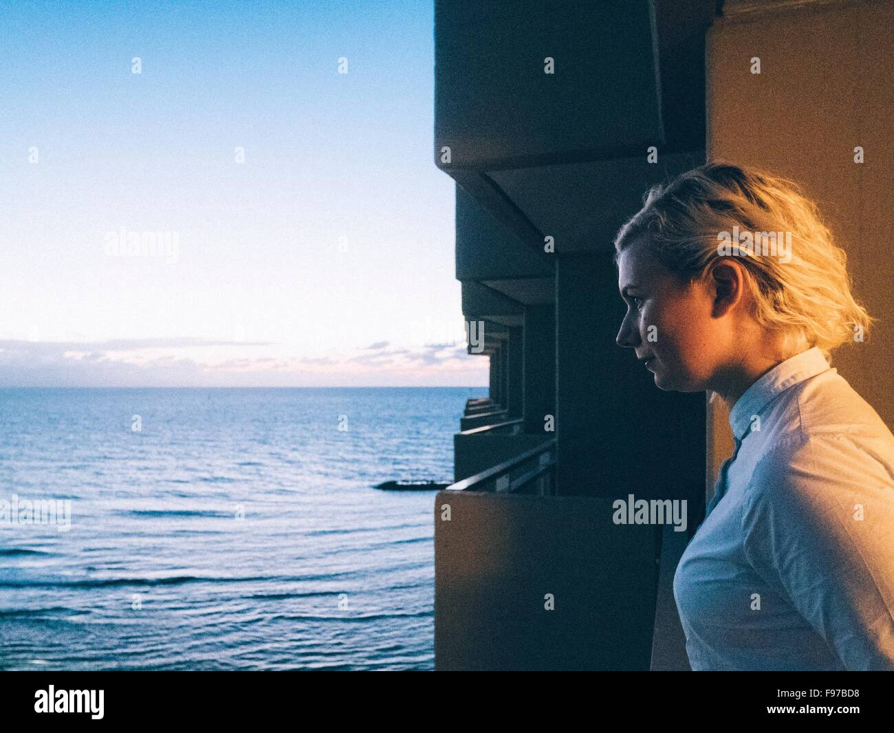 Side View Of Thoughtful Woman Looking At Sea - Stock Image