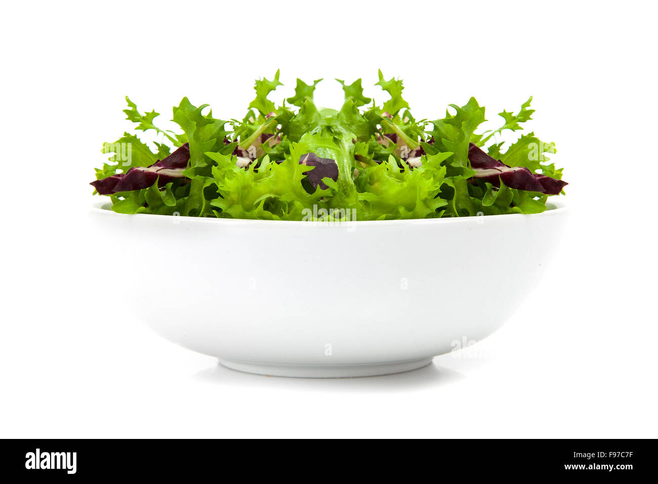 Bowl of mixed Salad with rucola, frisee, radicchio and lamb's lettuce. Isolated on white background - Stock Image