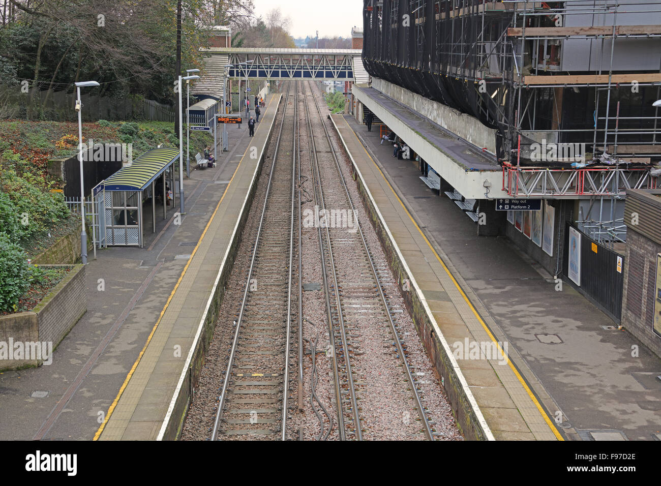 he view along the platforms towards the signal on third rail electrified lines with passengers waiting on the up - Stock Image