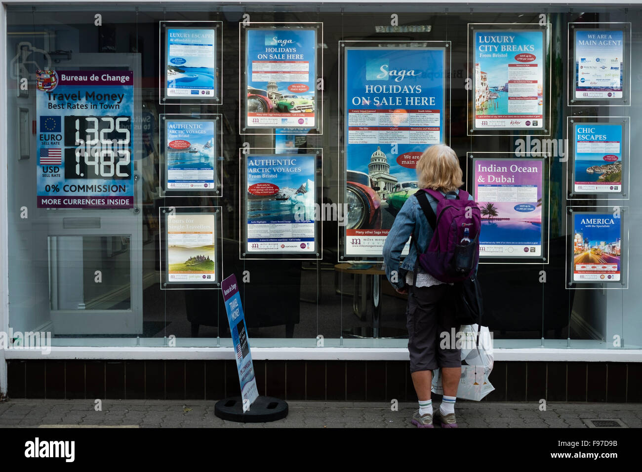 A rear view of a woman by herself  looking at posters showing details of Saga holidays for adults  in the window - Stock Image