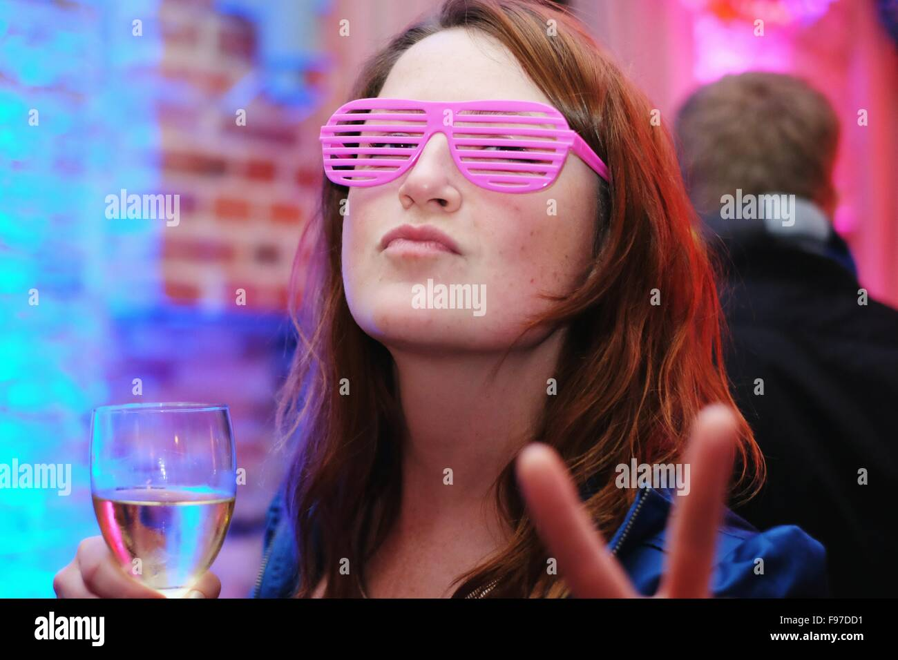 Portrait Of Young Woman Wearing Pink Eyeglasses Gesturing Peace Sign - Stock Image