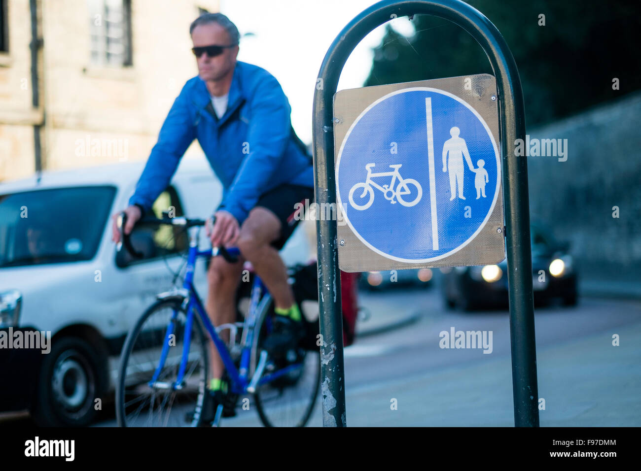A man cycling post a sign for a dedicated cycle and pedestrian lane, Cirencester, Gloucestershire, England, UK - Stock Image