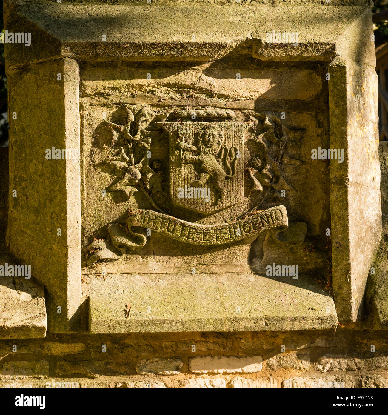 Stone panel with coat of arms with lion on shield and motto VIRTUTE ET INGENIO - By virtue and ability : Carved - Stock Image