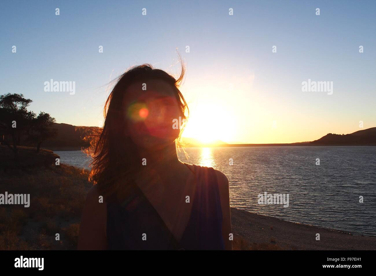 Sunlight Falling On Face Of Woman Standing At Beach - Stock Image