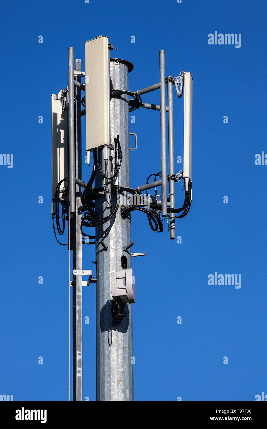 Cell tower and radio antenna for mobile phone network on a blue sky - Stock Image