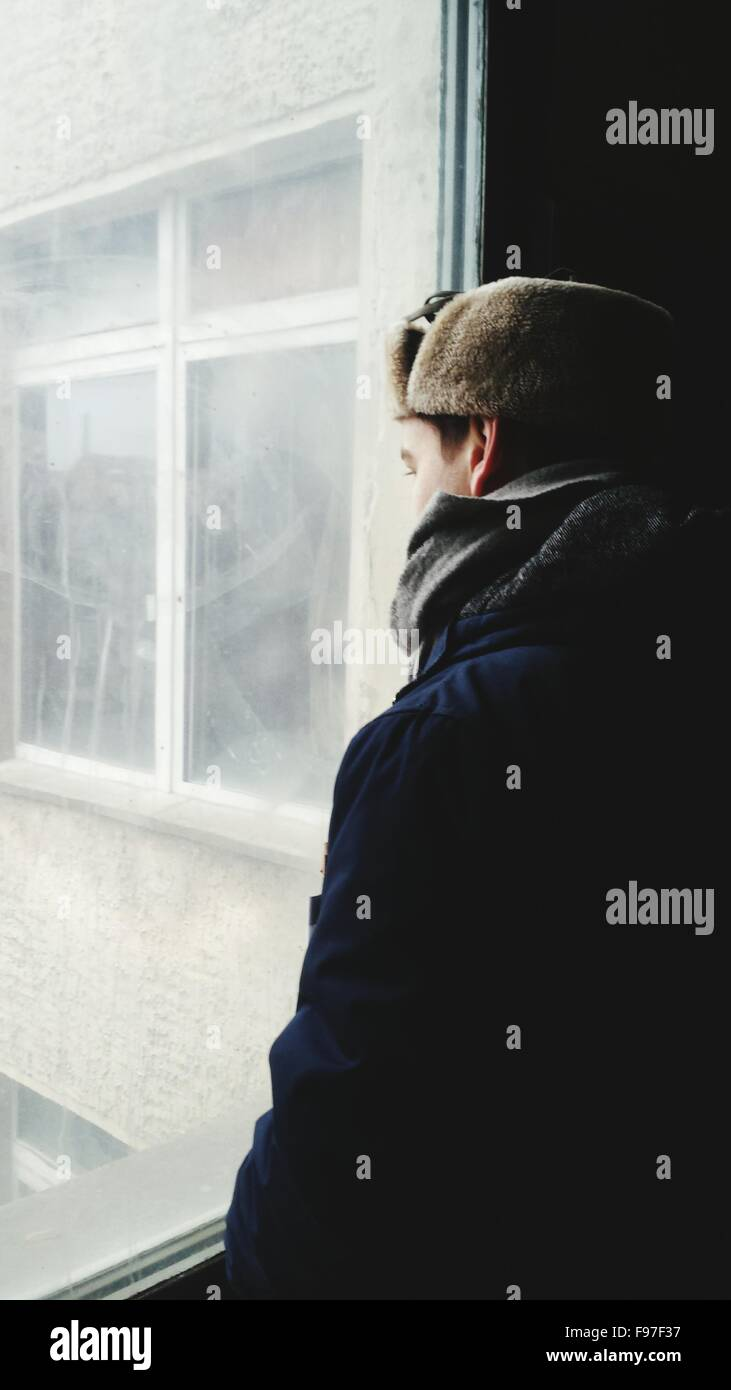 Man Looking Through Window In Building - Stock Image