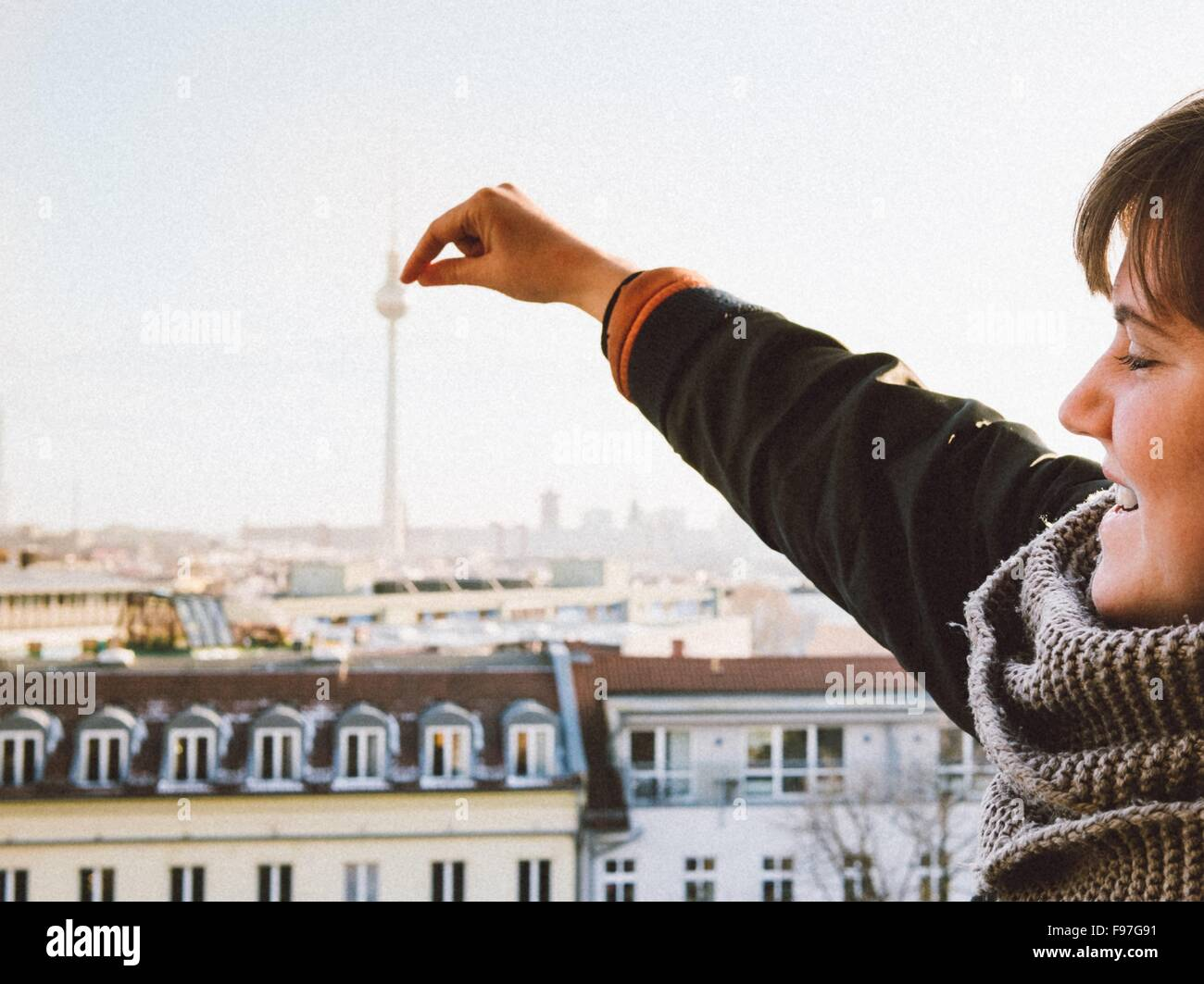 Optical Illusion Of Smiling Woman Touching Fernsehturm Tower Against Clear Sky - Stock Image