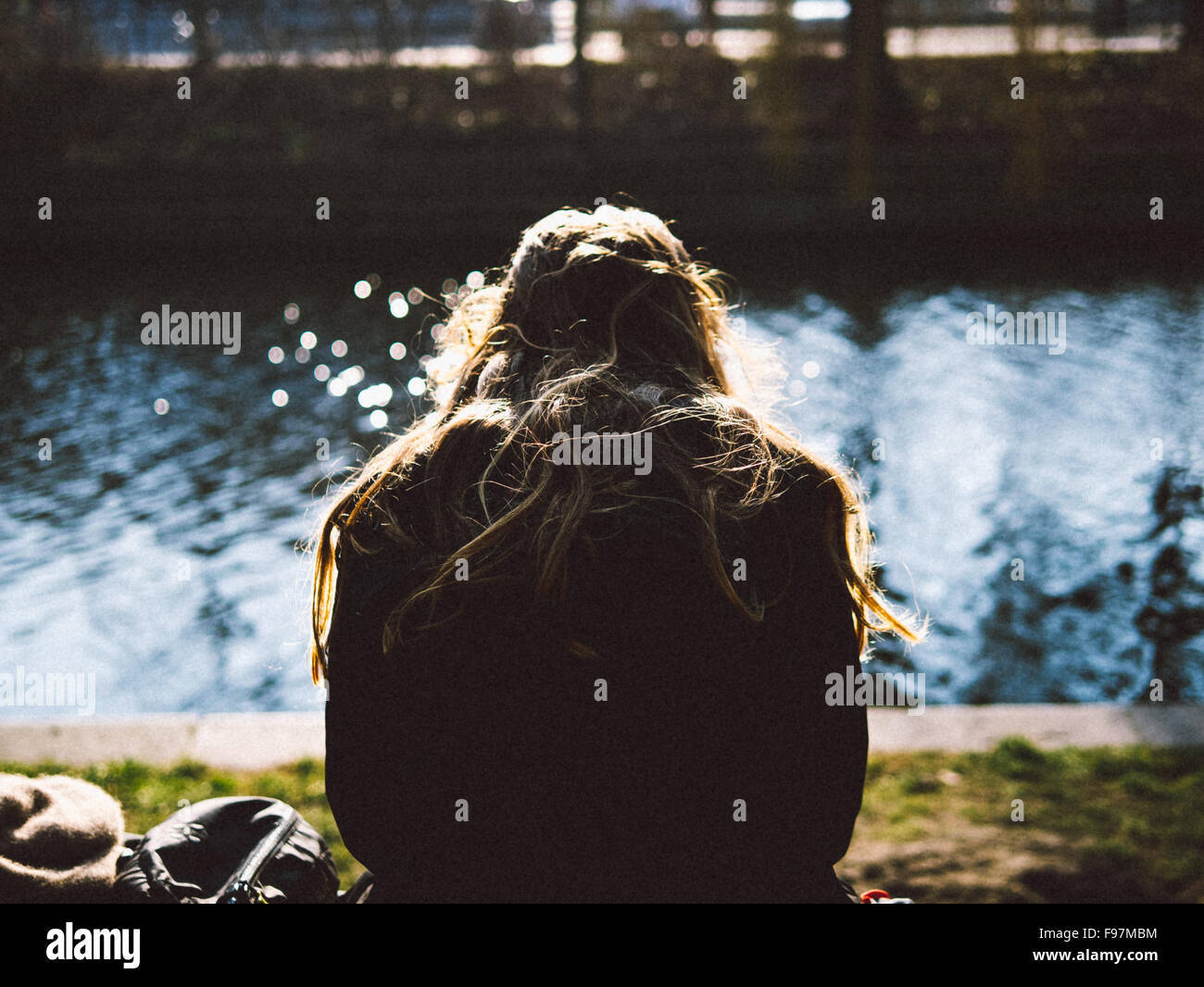 Rear View Of Woman Relaxing On Riverbank - Stock Image