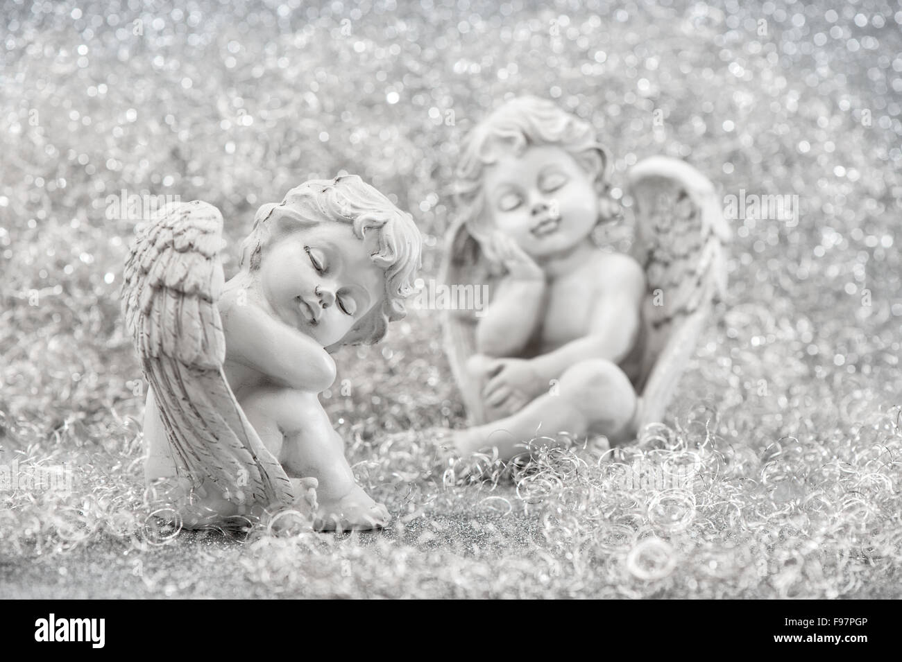 Slipping guardian angel with christmas decoration. Selective focus - Stock Image